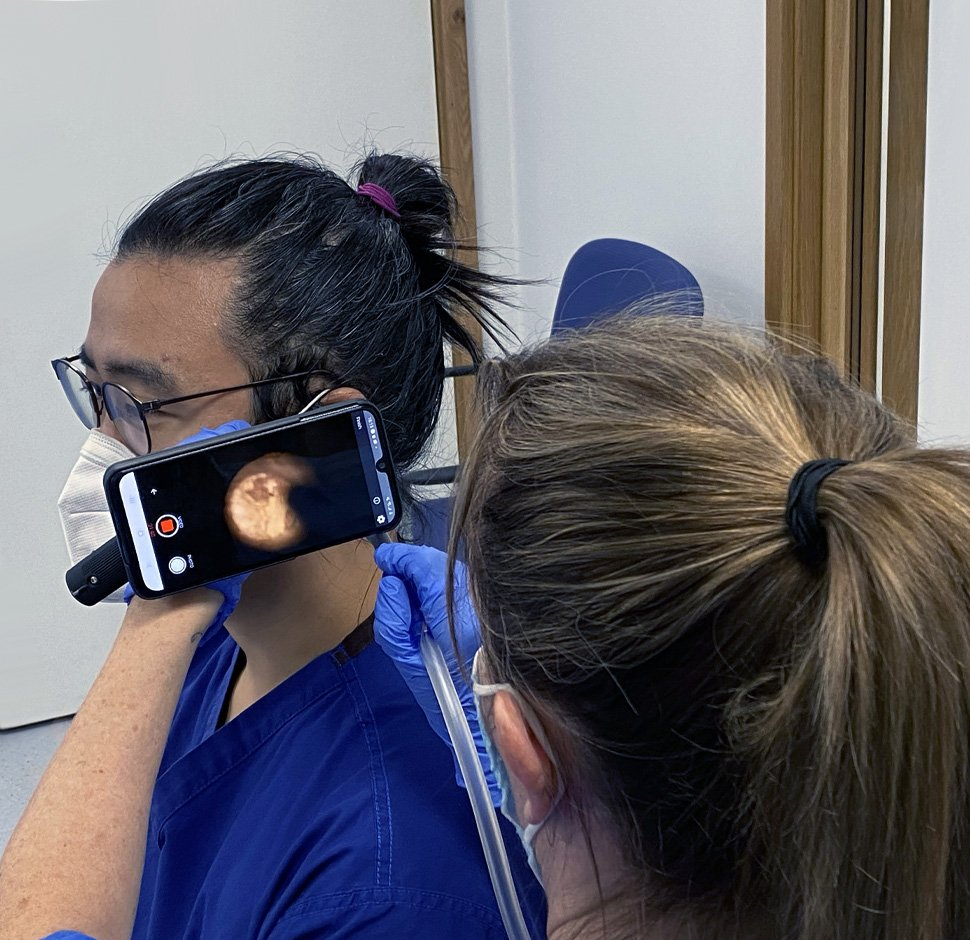 Client being treated for ear wax removal